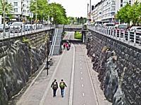 People on a sidewalk located below street level in Helsinki, Finland.