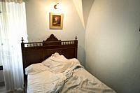 Unmade bed in townhouse bedroom. Santo-Pietro-di-Tenda, Corsica, Francia.