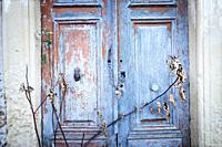 Close-up of an old door with flaking paint. Santo-Pietro-di-Tenda, Corsica, France.
