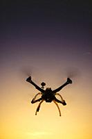 Photographic representation of the flight of a quadrocopter at sunset.
