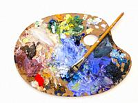 Colourful artists oil paint palette and brushes close up on plain background.
