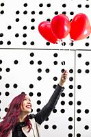 Lovely fashion girl with Valentine heart balloons. Sweet young woman with two heart shaped balloons on white dotted background.