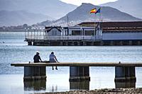 Couple sitting on the Jetty looking over the Mar Menor at Los Alcazares in Murcia Spain.