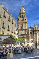 HDR image of the cafes and patron in front of Murcia Cathedral and bell tower in Spain.