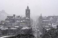 Snow falls on city of Edinburgh in December. Skyline view of city towards Princes Street from Calton Hill.