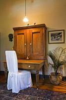 Old wooden antique desk with a high-back chair covered in a white cloth on the upstairs hallway inside a reconstructed 1840s residential log home, Que...