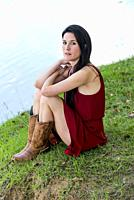 A 39 year old brunette woman looking at the camera wearing a red dress and boots, sitting on grass next to a pond