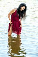 A 39 year old brunette woman wearing a red dress standing in a lake looking away from the camera.