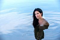 A pretty partially nude 39 year old brunette woman looking at the camera,standing in a lake.
