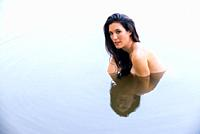 A pretty, partially nude 39 year old brunette woman looking at the camera, partially submerged in a lake.