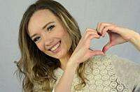 Young happy woman shape a heart with her hands.