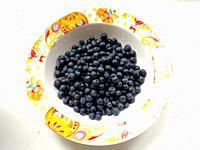 Fresh bilberry in the plate on white background. Concept for healthy eating and nutrition. Rustic style. Vitamins for breakfast.