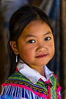 Flower Hmong (hill tribe) girl at the Sunday market at Bac Ha, northern Vietnam. Every Sunday ethnic minorities come from surrounding villages and hil...