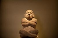 An sculpture of a man sitting and with his arms crossed is displayed in Museo Amparo, in Puebla de los Angeles, Mexico.