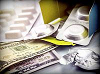 Some medicines next to a block of tickets of dollar, conceptual image.