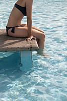 side view of young female sitting at poolside with legs in the water