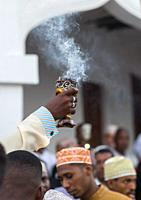 Sunni muslim man spreading insence with a censer during the Maulidi festivities in the street, Lamu County, Lamu Town, Kenya.