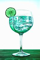 Gin tonic with lime slice.