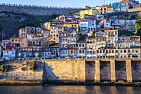 Houses over the Douro River in Se district of Porto, second largest city in Portugal on Iberian Peninsula. Fernandina walls on left side.