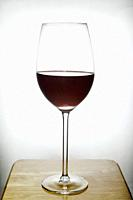 glass of red wine on wood with white background.