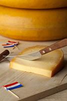 Piece of Dutch mature Gouda cheese on a cutting board with flags as cocktail picks.