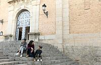 Mother and daughters sitting on the stairs next to the Church of Altea, province of Alicante, Spain.