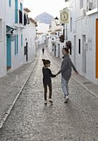 Two Sisters walking hand in hand through the town of Altea in the province of Alicante, Spain.