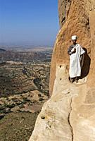 Priest standing on an exposed rock ledge at the entry to the rock-hewn church Abuna Yemata high above the ground, Gheralta region, Tigray, Ethiopia.