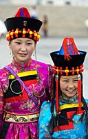 Two girls in traditional deel costume and the typical hat with the cone shaped top, Mongolian National Costume Festival, Ulaanbaatar, Mongolia.