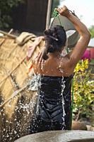 Woman bathing in small town well outside Bagan Myanmar.