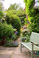 A garden bench beside an idyllic colourful summer UK cottage garden borde.