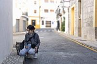 Teenage girl with her photo camera greeting a street cat in the town of Altea, in the province of Alicante, Spain.