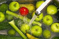 Washing fruit and vegetables in the kitchen sink before juicing and smoothie preparation.