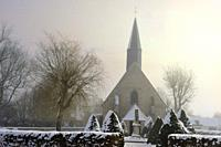 church of the village of Saint-Lucien covered with snow in the mist, department of Eure-et-Loir, Centre-Val-de-Loire region, France, Europe.