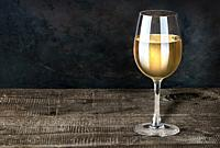 Glass of white wine on a wooden table. Dark background. Wooden table of plates.