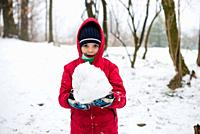 portrait of child with red jacket and hat in the snowy forest, in hands holds a big snowball.