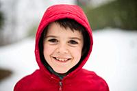 portrait of smiling child with red hat in snowy forest.