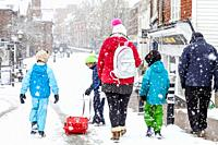 With local schools closed due to the bad weather a family take time to go sledging, High Street, Lewes, Sussex, UK.
