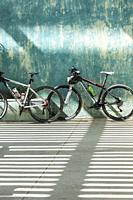 two bicycles on blue wall
