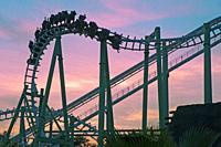 Isla Magica (Magic Island) Theme Park, The Jaguar at sunset - roller coaster (and people upside), Seville, Region of Andalusia, Spain, Europe.