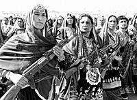 Afghan women village defense forces in traditional tribal costume carry Soviet AK-47's during a parade to mark the 10th anniversary of the communist r...
