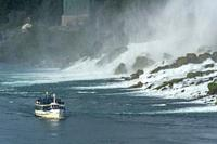 Maid of the Mist boat carrying tourists at the foot of American Falls at Niagara Falls.