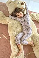 Five year old girl cuddling with her giant bear.