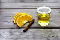 tequila shot with orange slice and cinnamon on wood background.