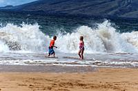 A boy and a girl on the beach in Maui as a big wave comes roaring in, Hawaii, USA.