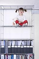 little girl seated high up in a bookshelf.