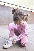 little girl learns about the zipper on her boot.