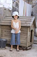 happy little girl outdoors in frot of a doghouse.