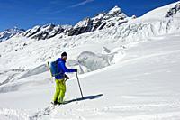 Ski tourer on the Langgletscher glacier beneath the peak Lauterbrunner Breithorn, Loetschental, Valais, Switzerland.