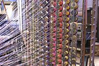 Dynamically lit skeins of brightly coloured thread on metal racks of wooden spools in traditional jacquard textile weaving, La Manufacture de Roubaix,...